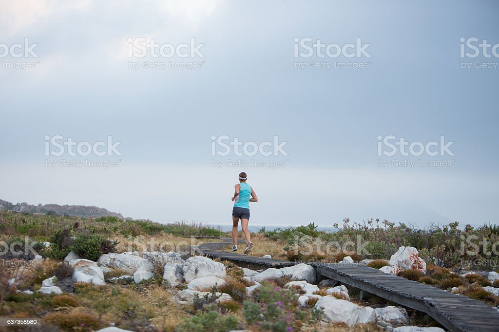 Female runner moves along a wooden coastal path stock photo
