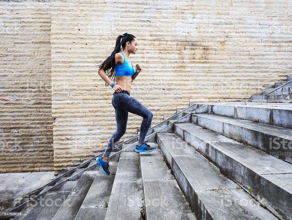 Female runner moving up on stone stairs-side view stock photo