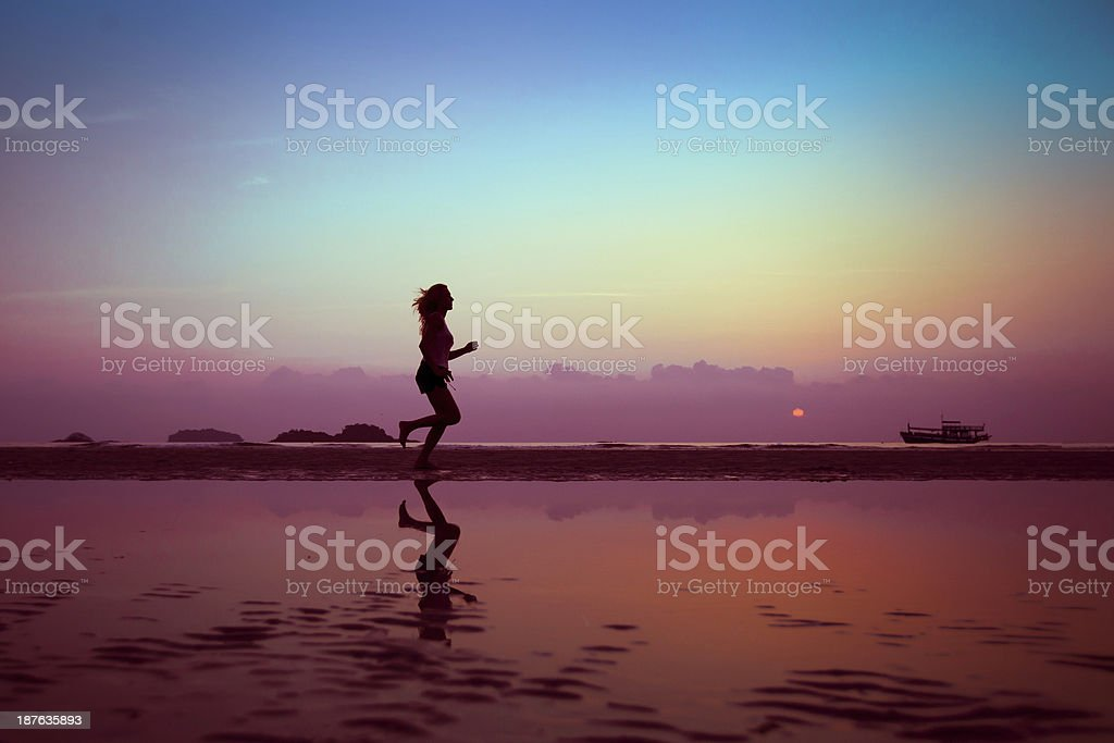 Female runner on the beach at sunset stock photo