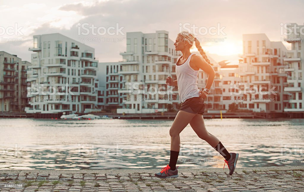 Female runner on the move as sun sets in city stock photo