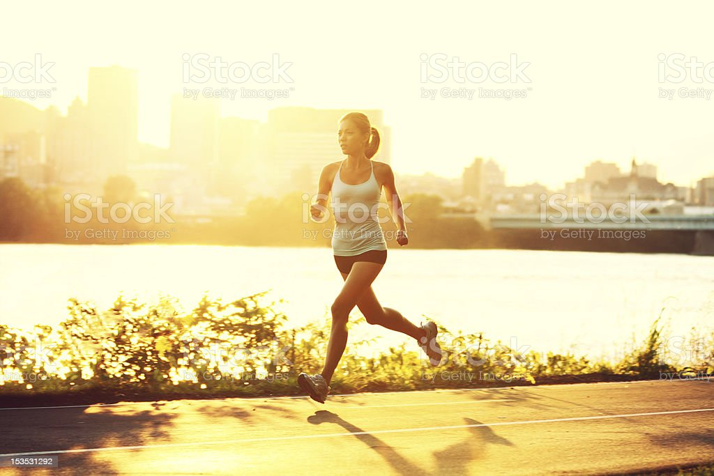 Female runner running at sunset stock photo