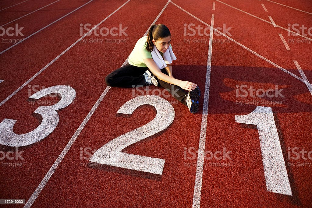 Female runner sitting on running track stretching hamstrings royalty-free stock photo