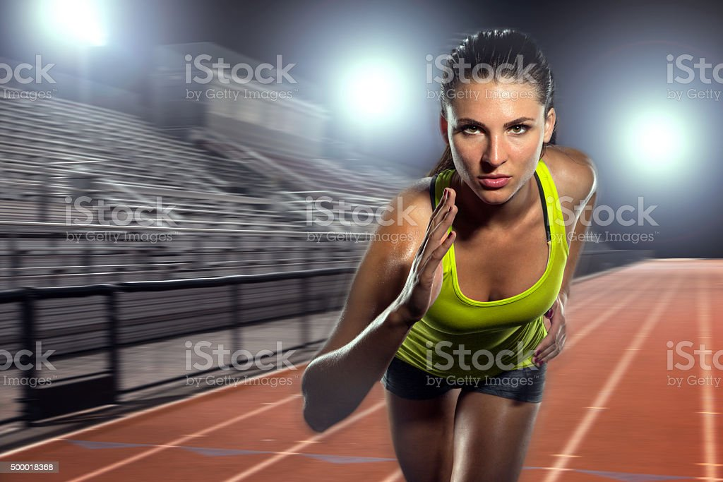 Female runner sprinter exercising training intense track field athlete sports stock photo