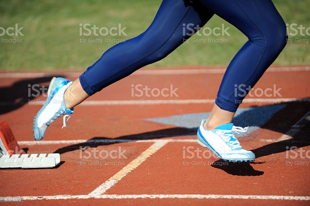 Female runner sprinting out of the starting block royalty-free stock photo