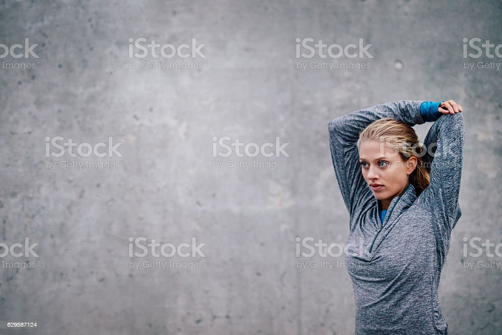 Female runner stretching arms after a running session stock photo