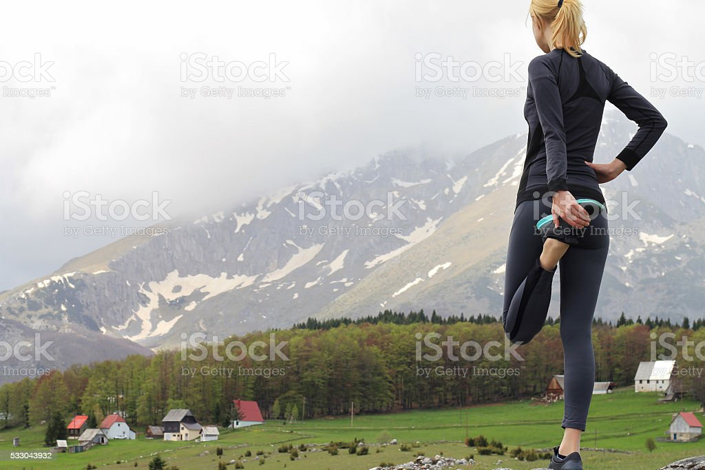 Female runner stretching legs after workout stock photo