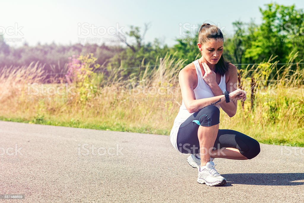 Female runner takes a break and measure pulse stock photo