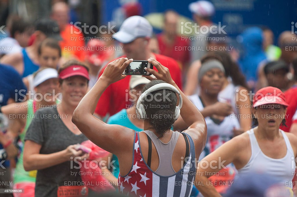 Female Runner Takes Picture Of Finish Line With Smartphone stock photo