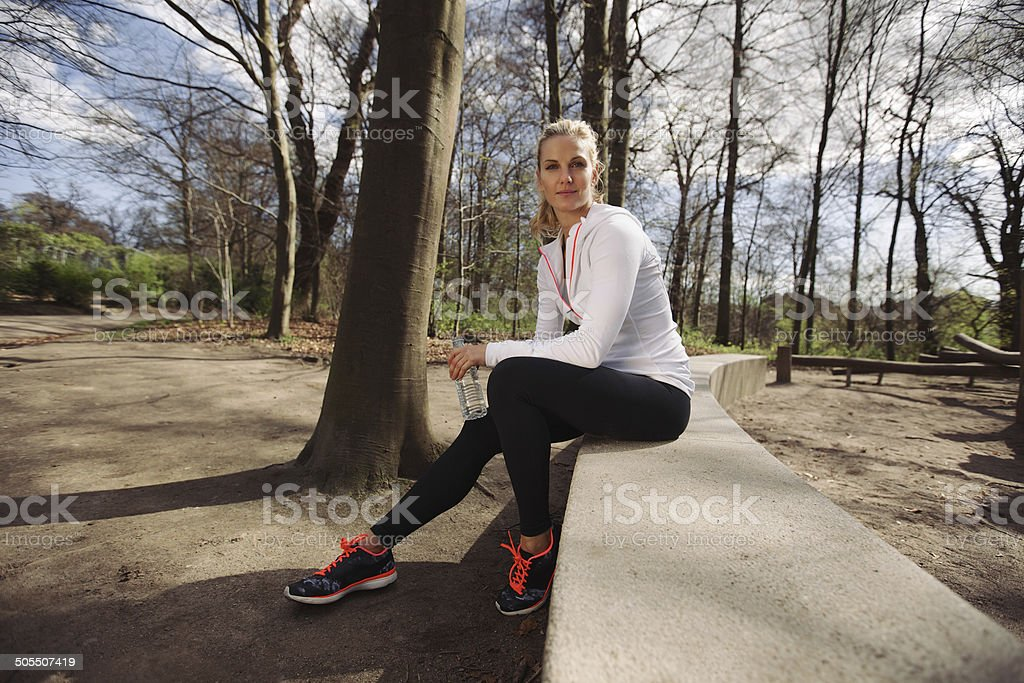 Female runner taking a rest from training in nature stock photo