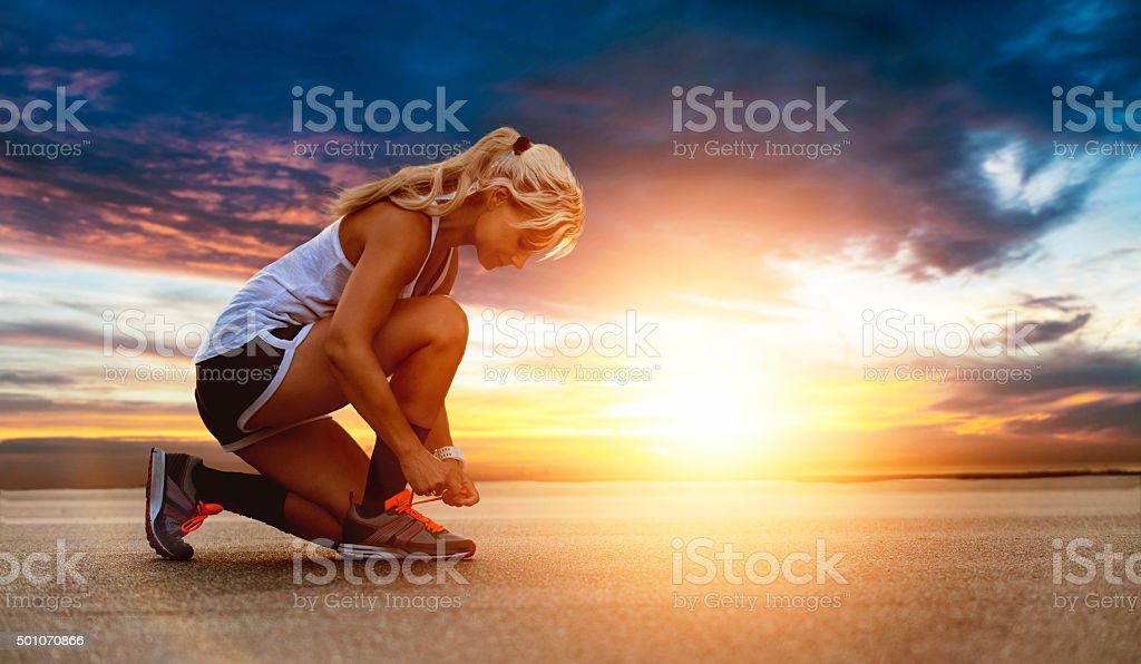 Female runner ties shoe before going for a run stock photo