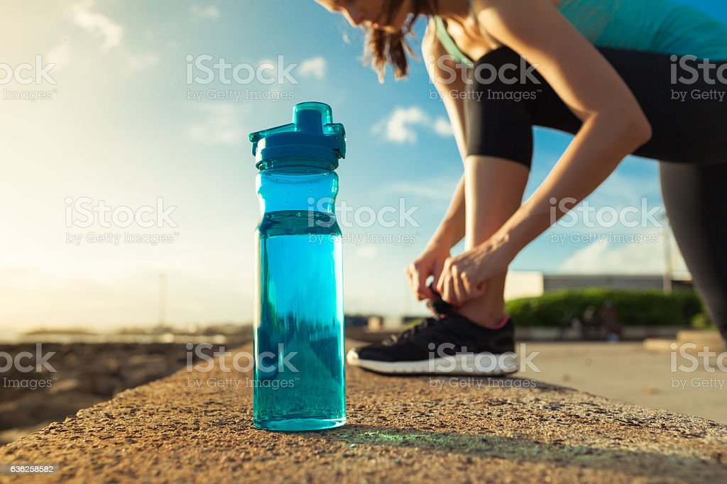 Female runner tying her shoes next to bottle of water stock photo