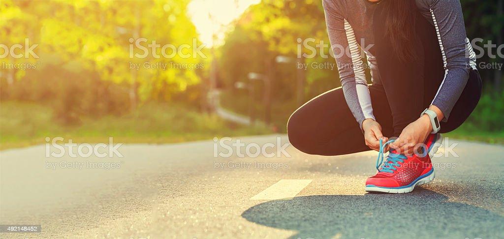 Corredora amarrando seus sapatos se preparar para uma corrida leve - foto de acervo