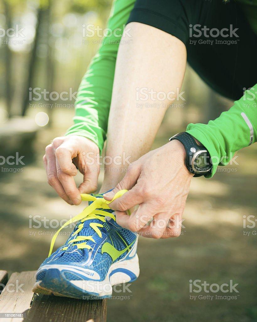 Female Runner Tying Running shoes royalty-free stock photo