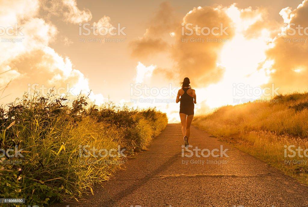 Female running at sunset. stock photo