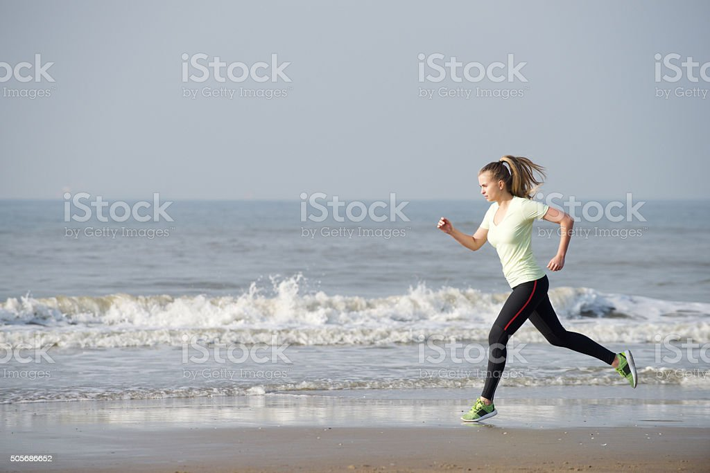 Female running by the sea stock photo