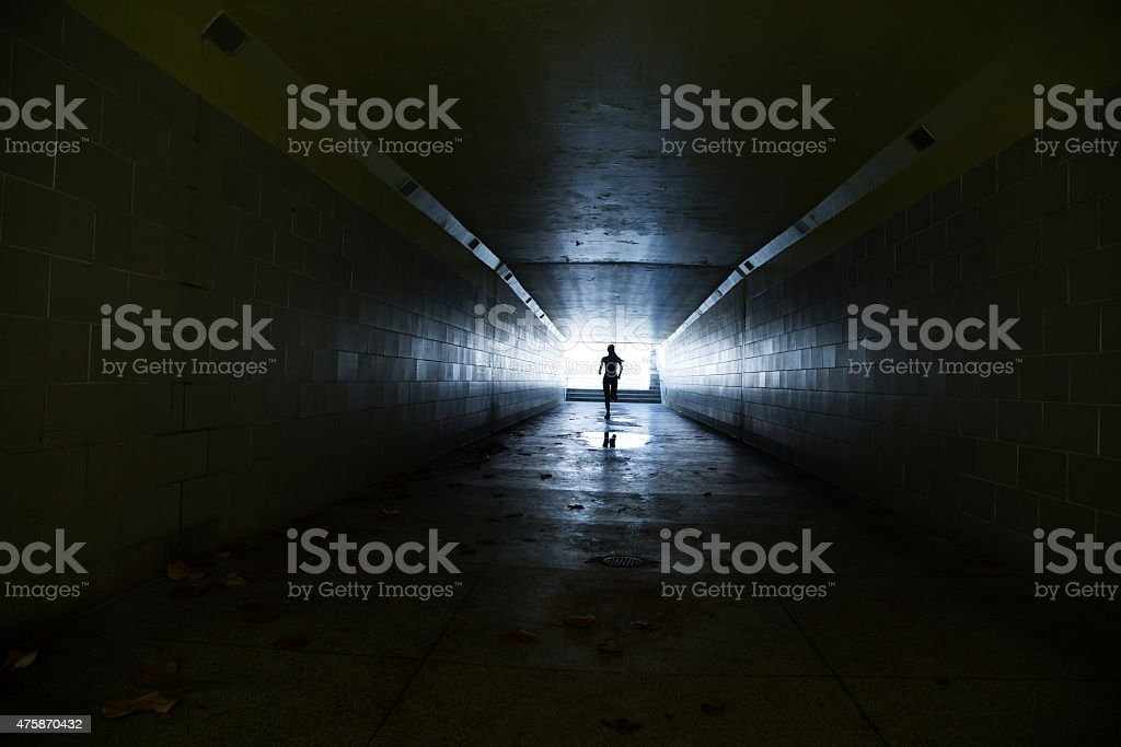 Female running in through a tunnel stock photo