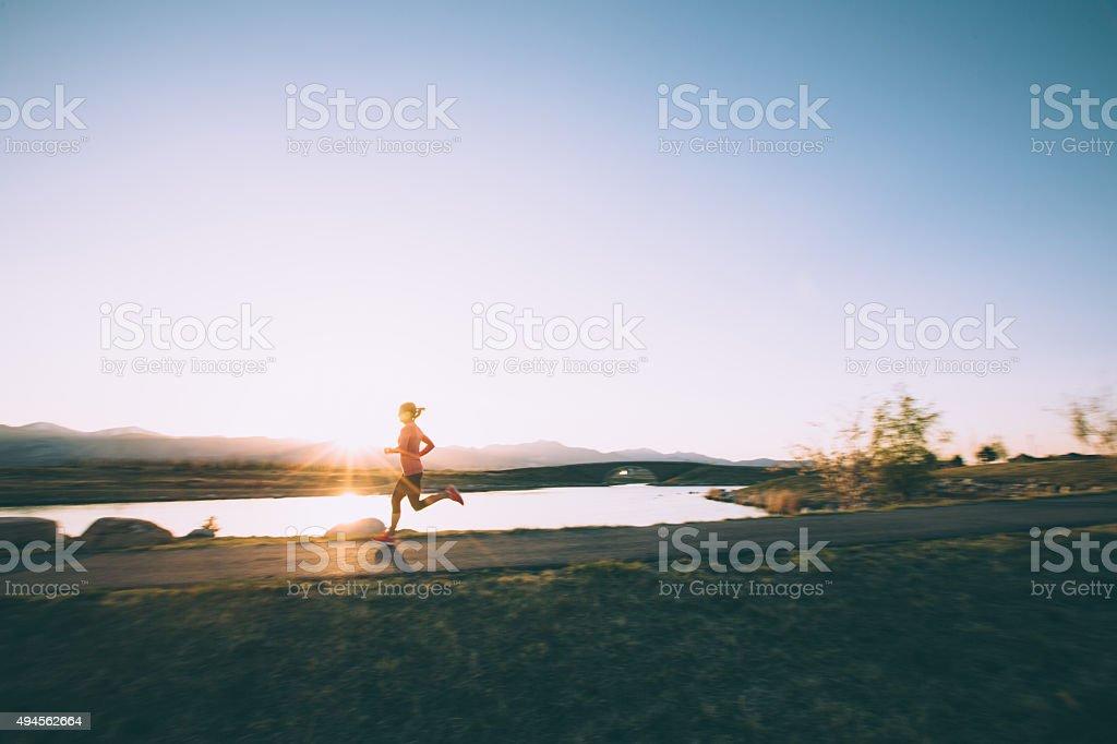 Femme course sur piste pendant le coucher du soleil dans l'Utah - Photo