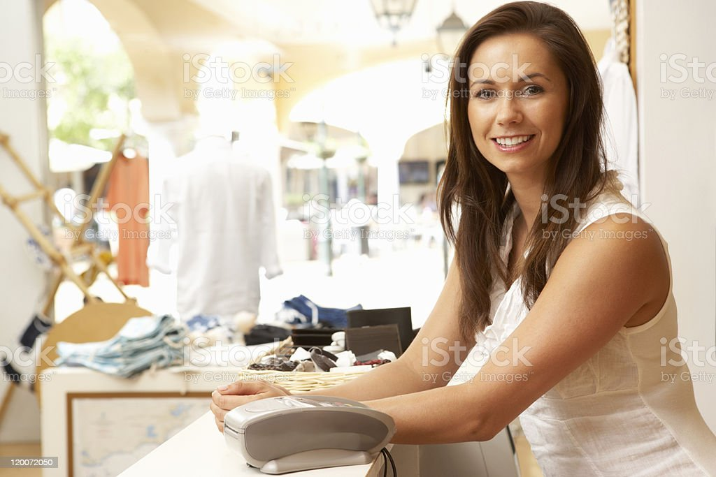 Female Sales Assistant At Checkout Of Clothing Store stock photo