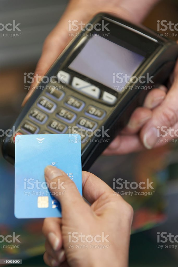 Female Sales Assistant Holding Credit Card Machine stock photo
