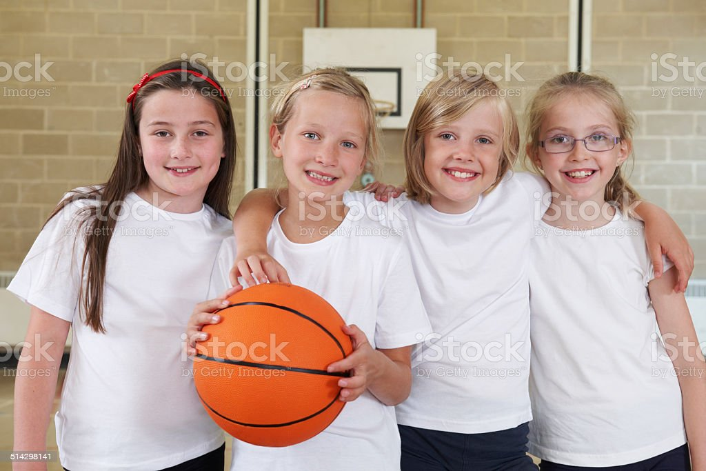 Female School Sports Team In Gym With Basketball stock photo