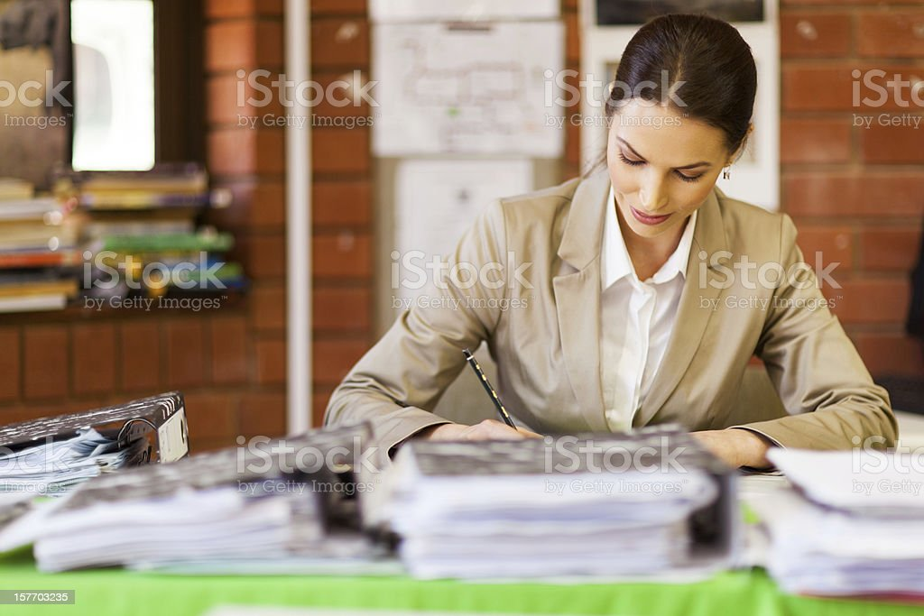 female school teacher working in office stock photo