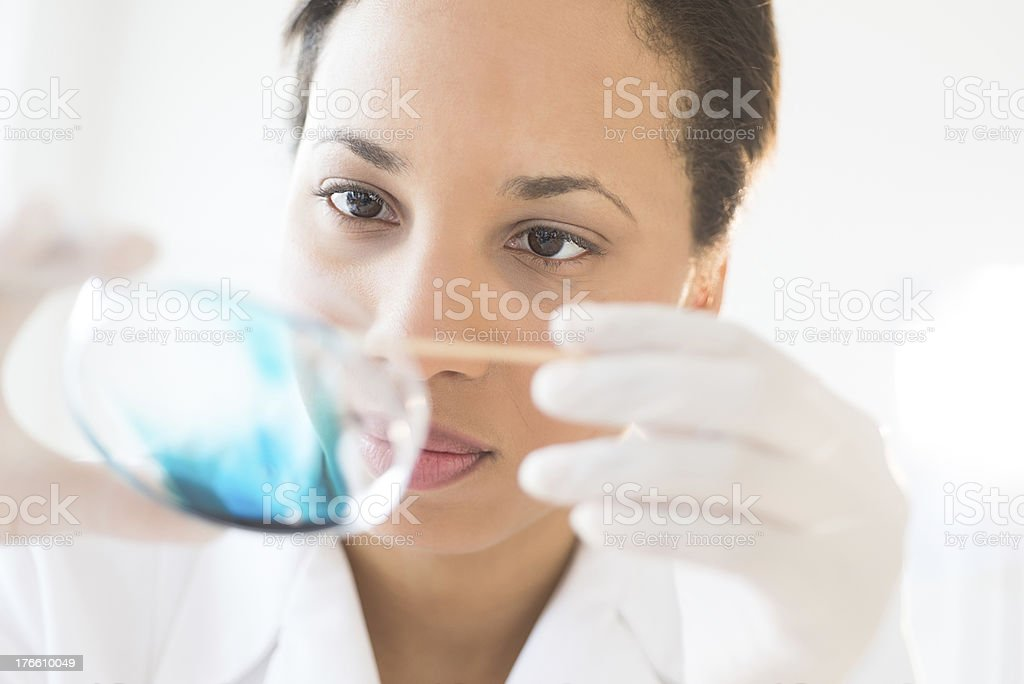 Female scientist examining a blue solution in a petri dish royalty-free stock photo