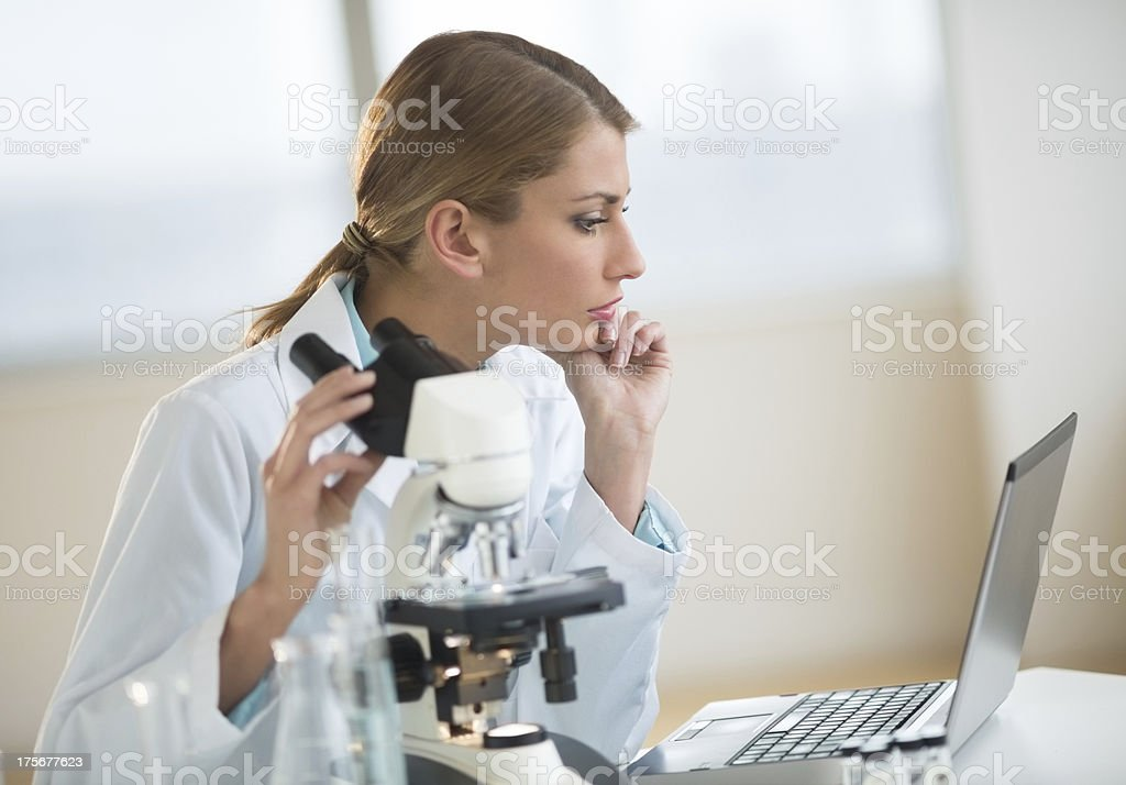 Female Scientist Looking At Laptop In Laboratory royalty-free stock photo