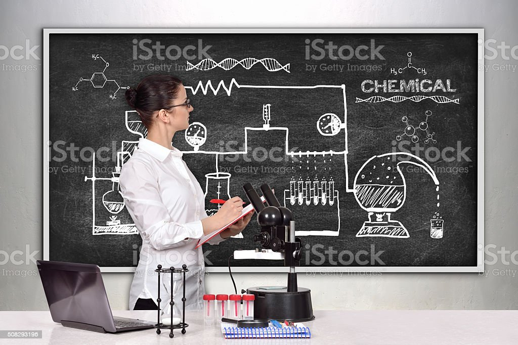 female scientist looking on scheme chemical reaction stock photo