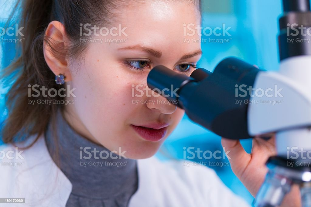 Female scientist looking through a microscope in laboratory stock photo