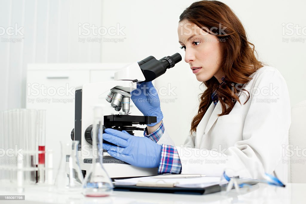 Female Scientist Looking Through a microscope royalty-free stock photo