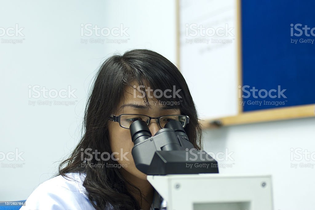 female scientist looking through microscope royalty-free stock photo