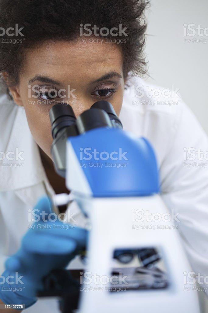 Female scientist looking through microscope stock photo