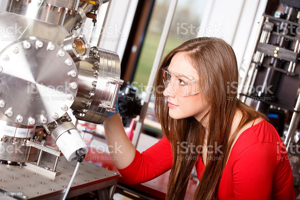 Female scientist looking to the laser deposition chamber stock photo