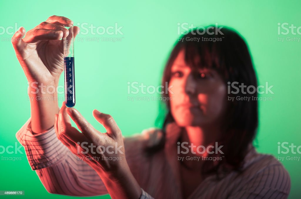 Female scientist looks at the graduated tube stock photo
