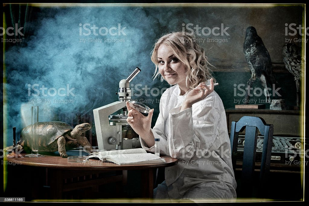 Female scientist researching in nostalgic laboratory stock photo
