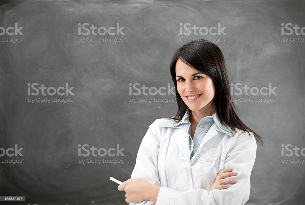 Female scientist smiling with arms folded, holding chalk royalty-free stock photo
