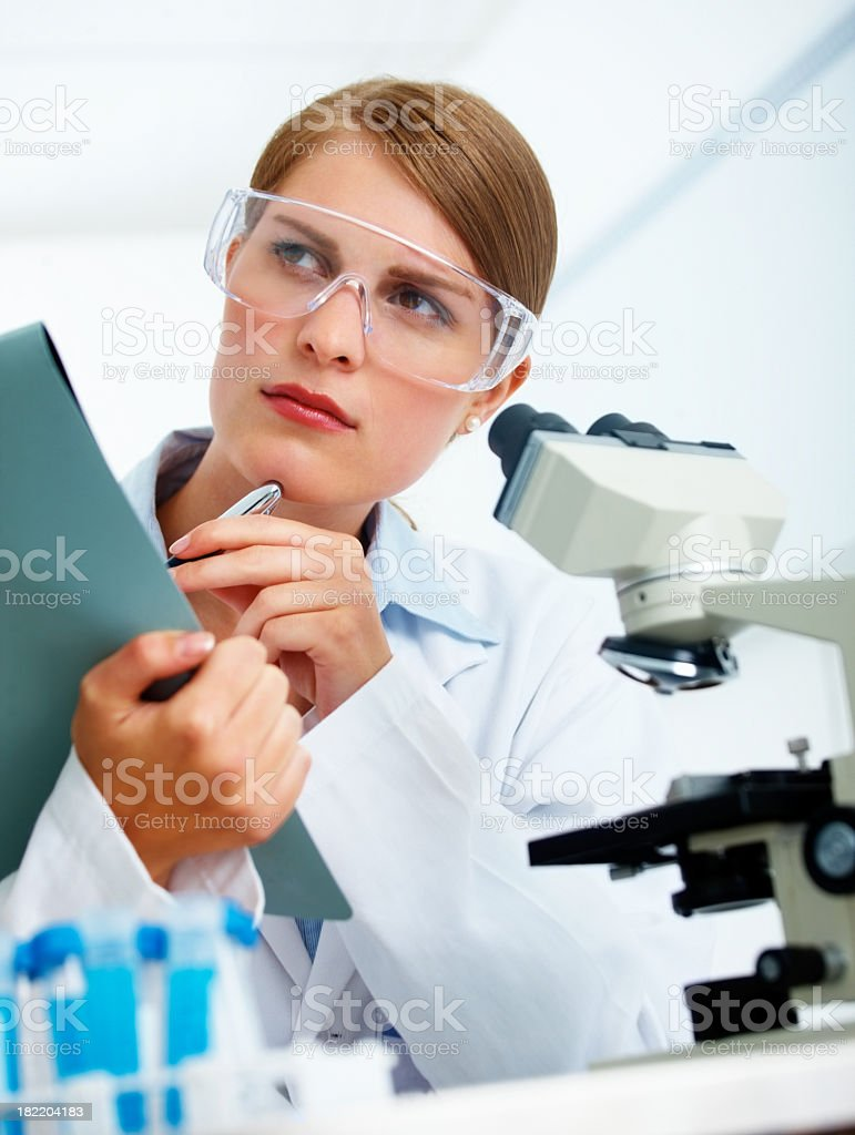 Female scientist thinking while making notes royalty-free stock photo