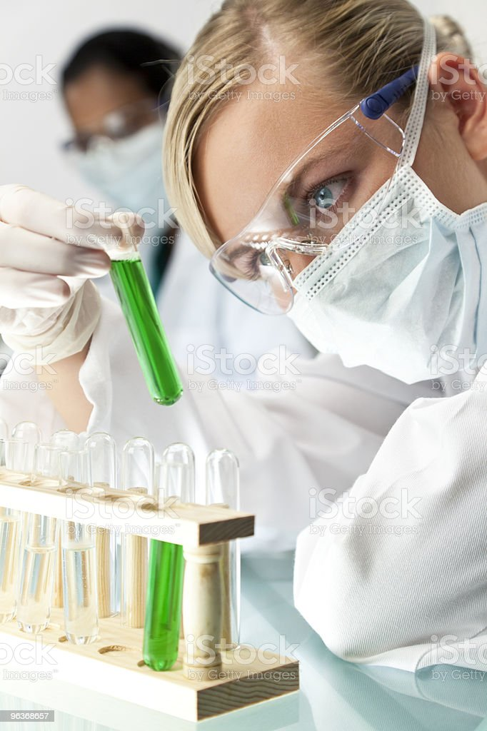 Female Scientist With Test Tube of Green Solution In Laboratory royalty-free stock photo