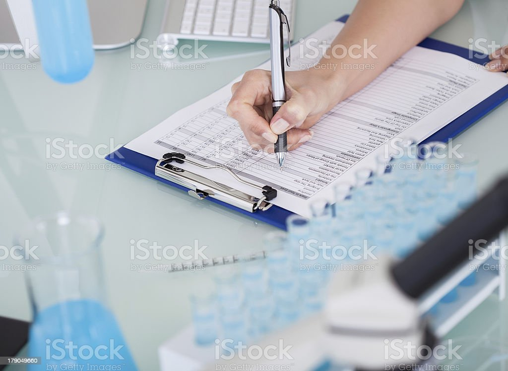 Female Scientist Writing On Notepad stock photo