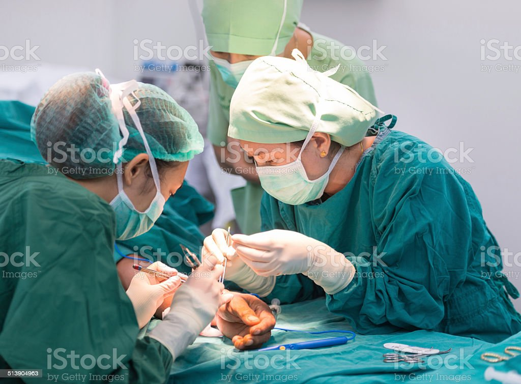 female scrub nurse help female surgeon do surgery stock photo