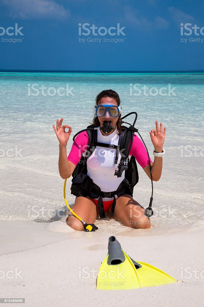 Female scuba diver does the OK sign on a beach stock photo