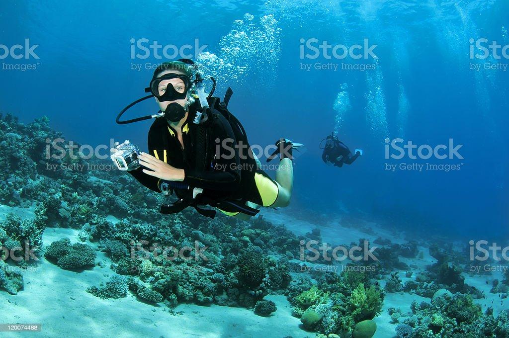 female scuba diver with underwater camera stock photo
