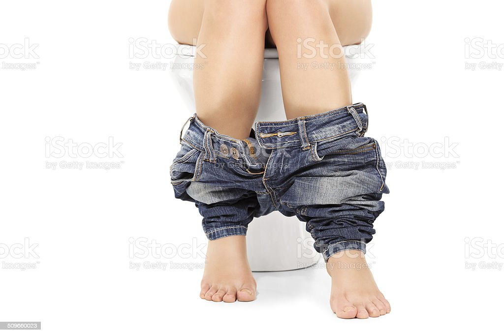 Female seated at a toilet with her pants down stock photo