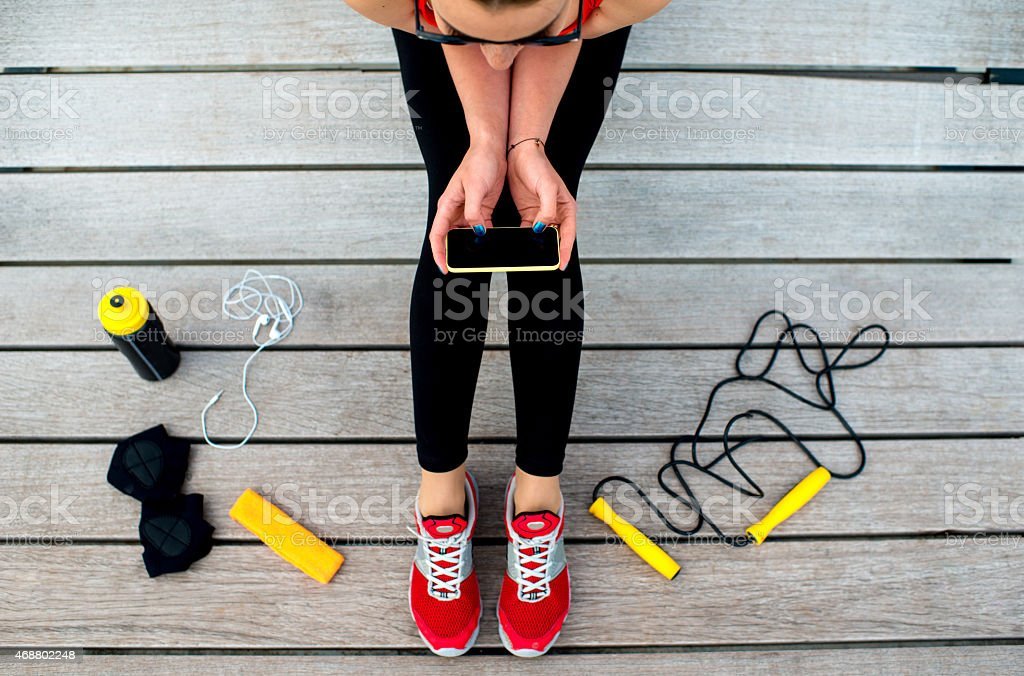 Female seated with sports equipment using a cell phone app stock photo