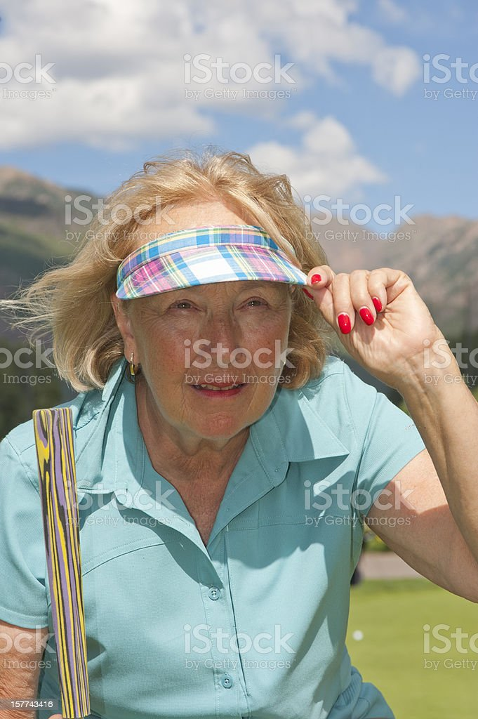 Female Senior Citizen Lining Up Golf Putt royalty-free stock photo