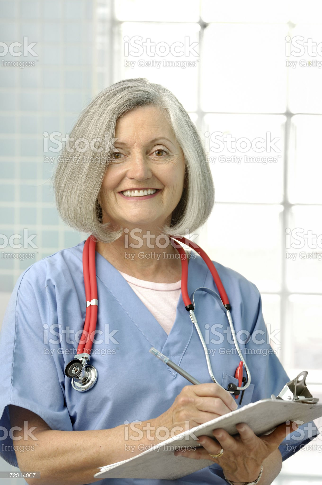female senior doctor with clipboard smiling royalty-free stock photo
