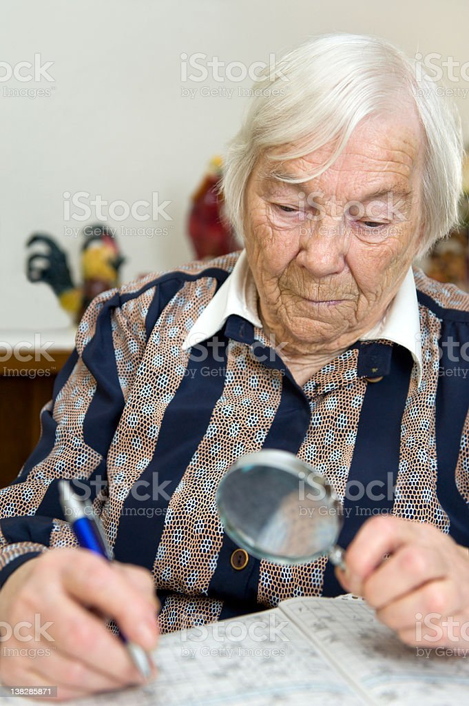 Female senior is alone at home and solves a Crossword royalty-free stock photo