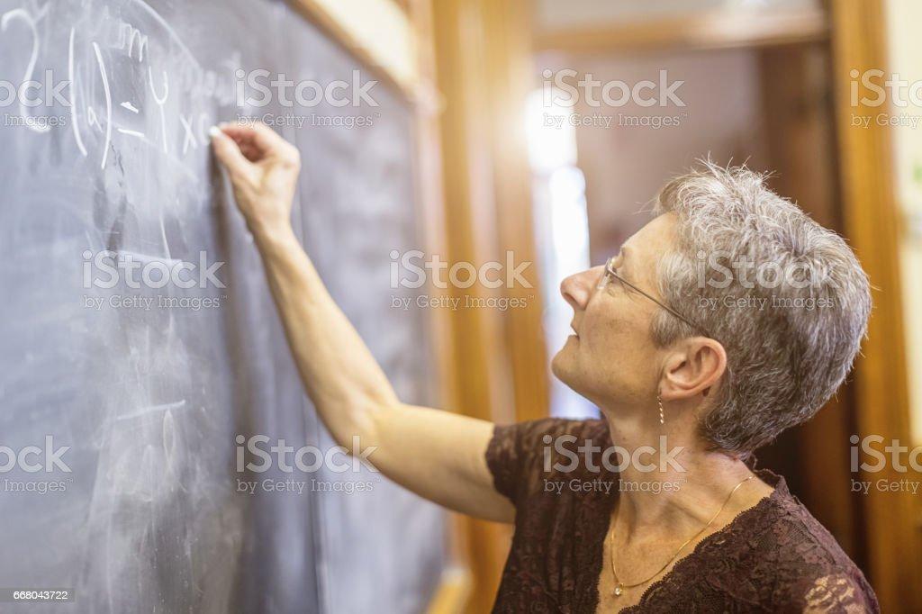 Female Senior Mathemathics Professor at Chalkboard Writing Formula stock photo