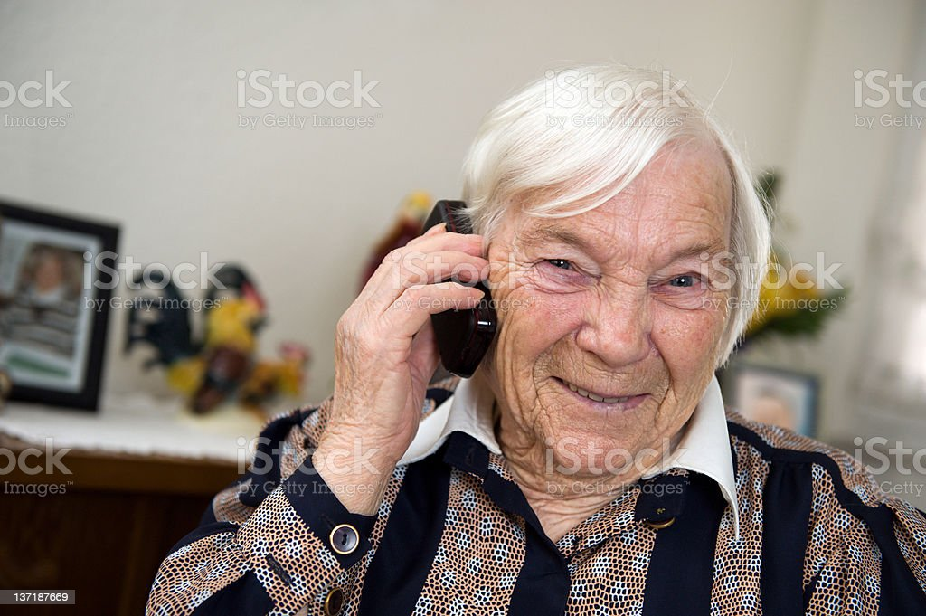 Female senior with a mobile phone at home royalty-free stock photo