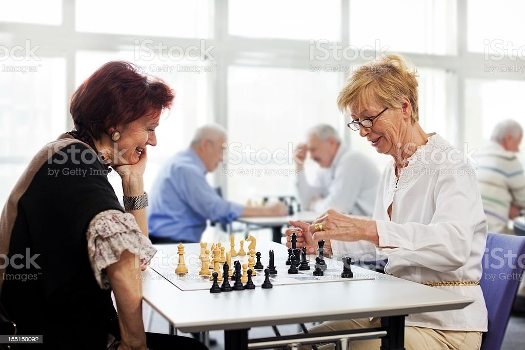 Female seniors playing chess in the community center stock photo